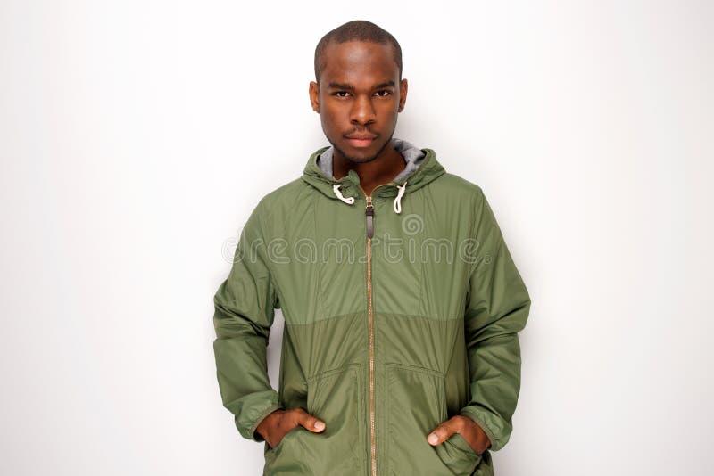 Giovane uomo di colore bello con il rivestimento contro fondo bianco isolato immagine stock