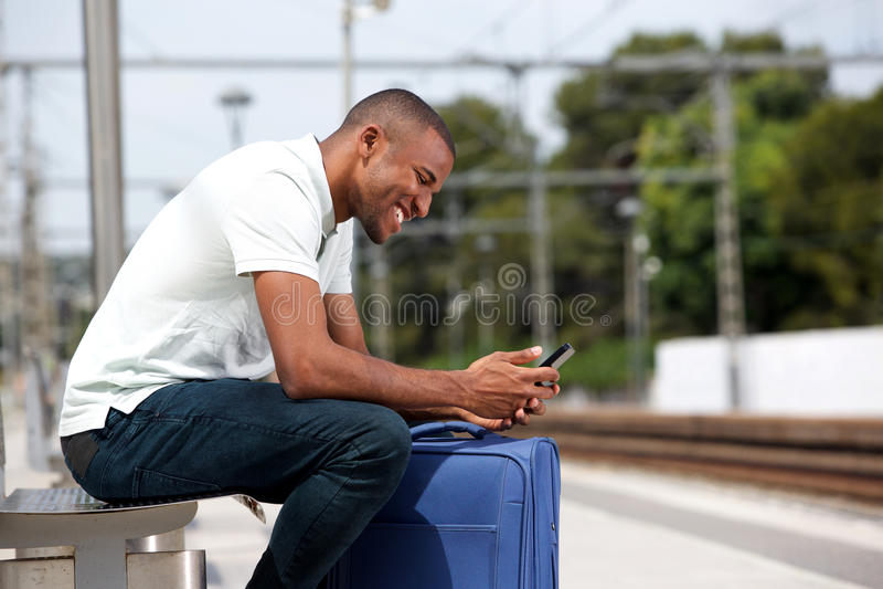 Giovane uomo di colore che aspetta alla piattaforma ferroviaria con il cellulare fotografia stock