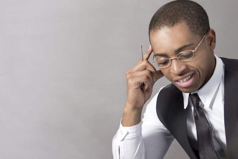 Giovane uomo di colore che pensa nel suo ufficio fotografie stock