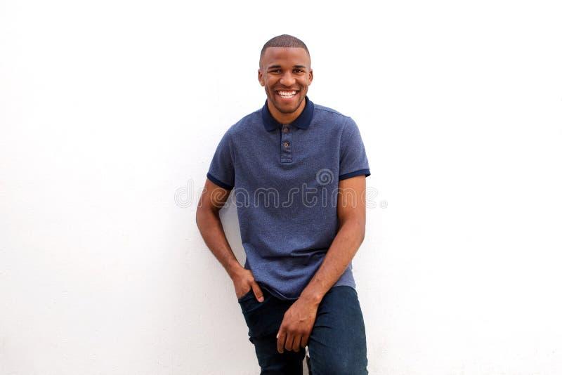Giovane uomo di colore che sorride contro il fondo bianco fotografie stock