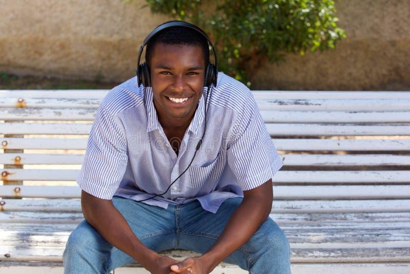 Giovane uomo di colore felice che si siede sul banco di parco con le cuffie fotografia stock libera da diritti
