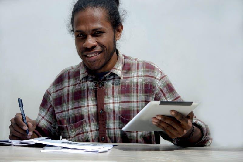 Giovane uomo di colore sorridente che lavora e che studia giudicando computer portatile e penna che fanno compito immagini stock libere da diritti