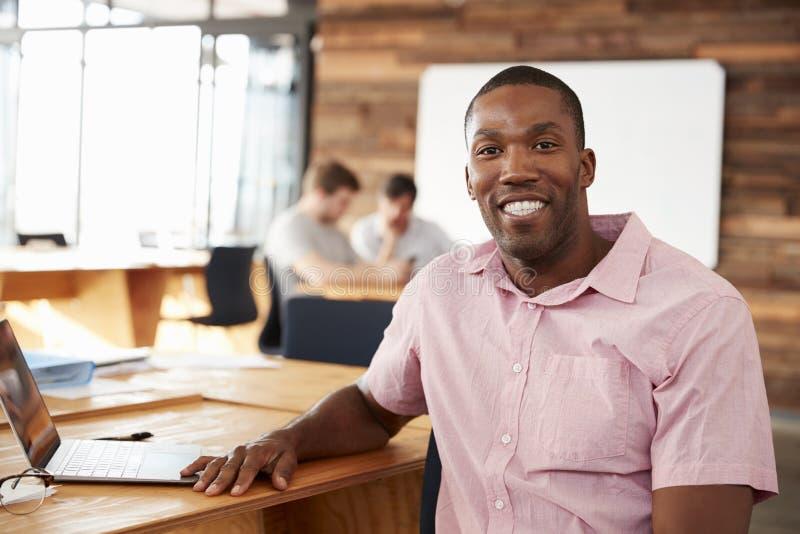 Giovane uomo di colore sorridente in ufficio creativo che guarda alla macchina fotografica immagine stock libera da diritti