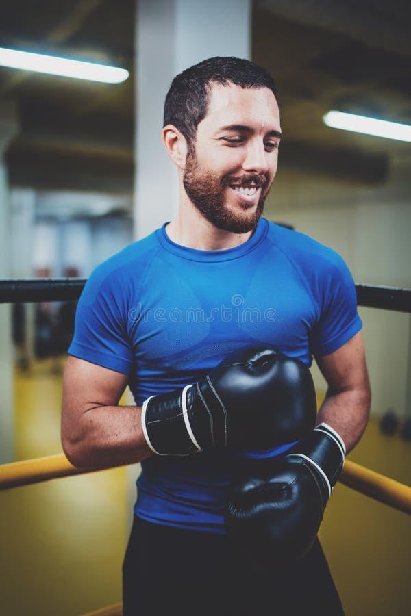 Giovane uomo di pugilato con i guantoni da pugile che sorride sull'anello Atleta caucasico in guanti neri che prepairing per l'ad fotografia stock