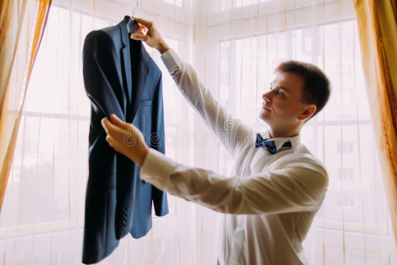 Giovane uomo di sguardo ellegant che dà il suo rivestimento in una camera di albergo, preparante a vestirsi per un evento fotografia stock