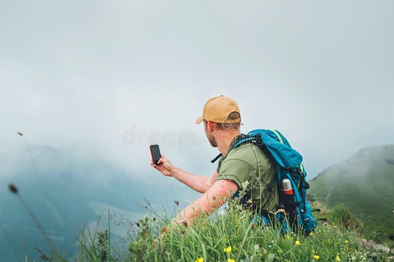 Giovane uomo di viaggiatore con zaino e sacco a pelo che prende immagine del fondo nuvoloso della valle facendo uso dello smartph immagini stock libere da diritti