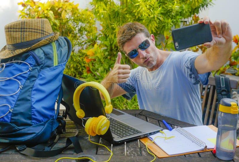 Giovane uomo digitale attraente e felice del nomade che lavora all'aperto con il pic di presa allegro del selfie del computer por immagini stock libere da diritti