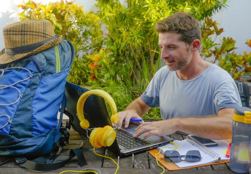 Giovane uomo digitale attraente e felice del nomade che lavora all'aperto con la ripresa esterna corrente allegra e sicura del co fotografia stock