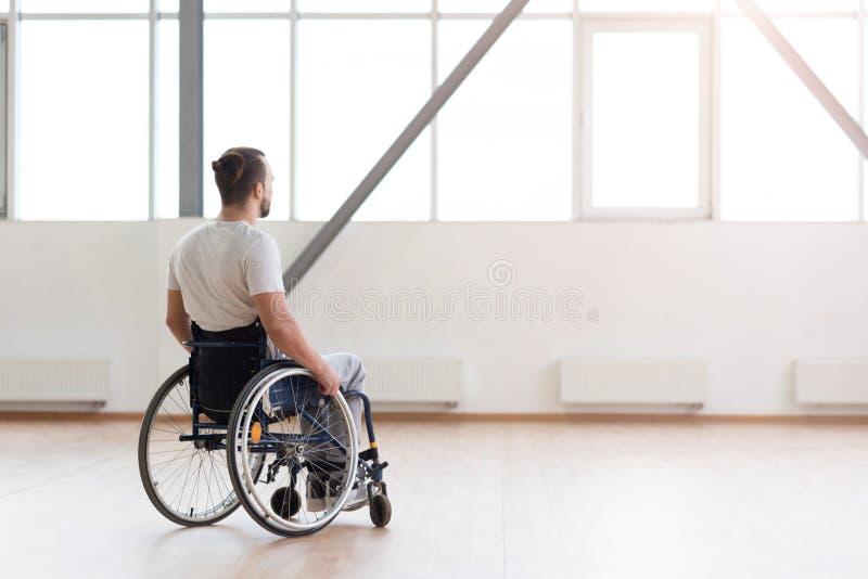 Giovane uomo disabile che si siede nella sedia a rotelle nella palestra fotografia stock libera da diritti