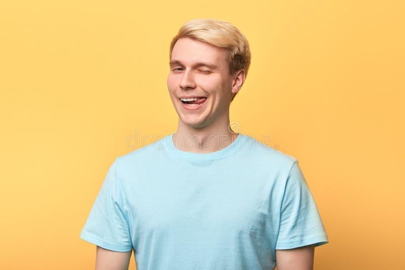 Giovane uomo divertente allegro che mette fuori la suoi lingua e sbattere le palpebre fotografia stock