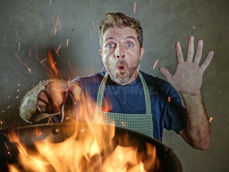 Giovane uomo domestico divertente e sudicio del cuoco con il grembiule in pentola della tenuta di scossa in fuoco che brucia l'al immagini stock libere da diritti