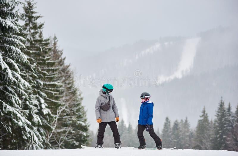 Giovane uomo e donna snowboarder in piedi su una pendenza coperta di neve e si guardano l'un l'altro Snowfall sullo sfondo fotografie stock libere da diritti
