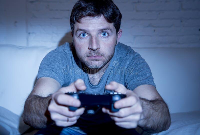 Giovane uomo emozionante a casa che si siede sul sofà del salone che gioca i video giochi facendo uso della leva di comando telec fotografie stock libere da diritti