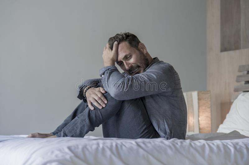 Giovane uomo enorme e depresso attraente che si siede sul fronte preoccupato e frustrato del letto di sofferenza di depressione d immagine stock