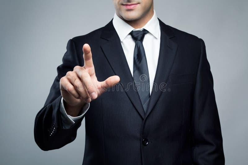 Giovane uomo esecutivo che tocca uno schermo immaginario fotografia stock libera da diritti