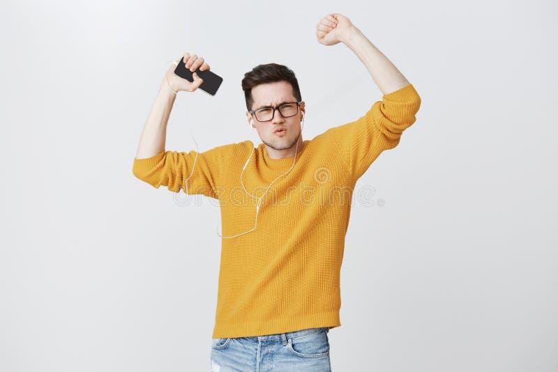 Giovane uomo europeo ottimistico bello in vetri e sensibilità gialla calda del maglione come l'energia d'amplificazione del vinci fotografia stock