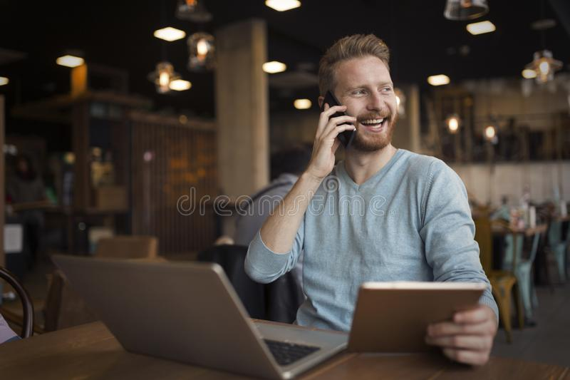 Giovane uomo felice che ha telefonata in caffè fotografia stock