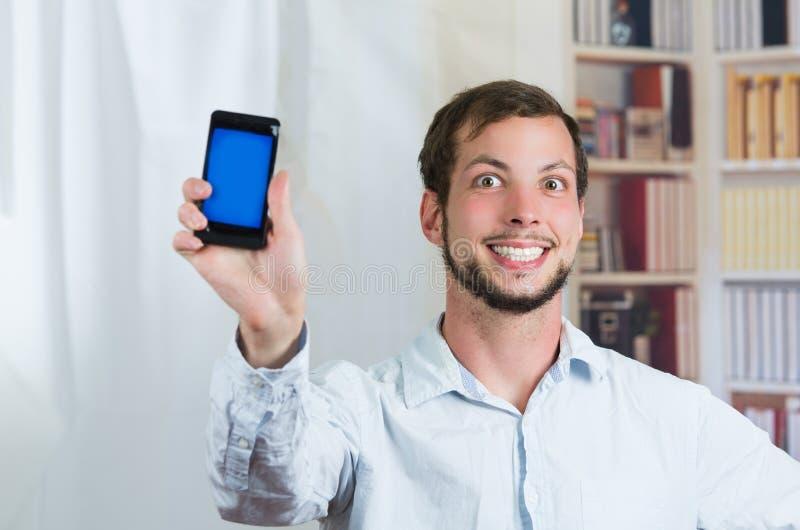 Giovane uomo felice che tiene il suoi telefono cellulare e mostra fotografie stock libere da diritti