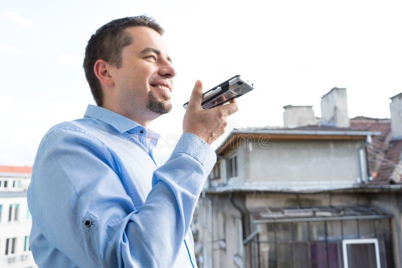 Giovane uomo felice di affari che invia messaggio vocale dal suo smartphone immagini stock