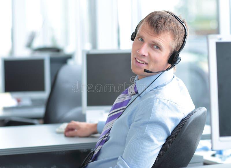 Giovane uomo felice di affari in cuffia che esamina macchina fotografica immagini stock libere da diritti