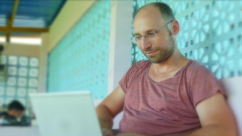 Giovane uomo felice e sicuro di viaggiatore con zaino e sacco a pelo che lavora con il computer portatile e la rete come l'impren fotografia stock libera da diritti