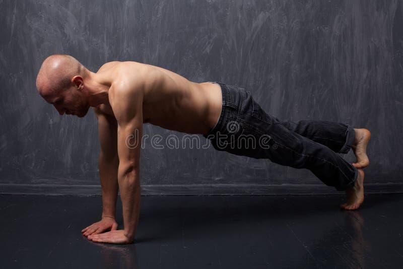 Giovane uomo forte con un torso nudo che fa spinta-UPS fotografia stock
