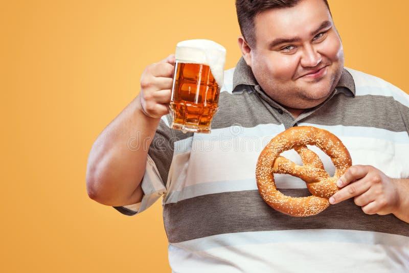 Giovane uomo grasso a birra ed alla ciambellina salata di cibo più oktoberfest e beventi su fondo giallo fotografia stock