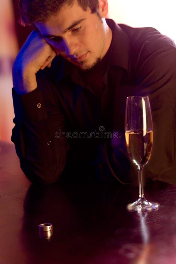 Giovane uomo imbarazzato con il vetro del champagne e dell'anello immagine stock libera da diritti