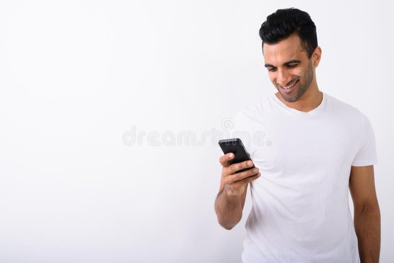 Giovane uomo indiano bello che per mezzo del telefono cellulare contro il backg bianco fotografie stock