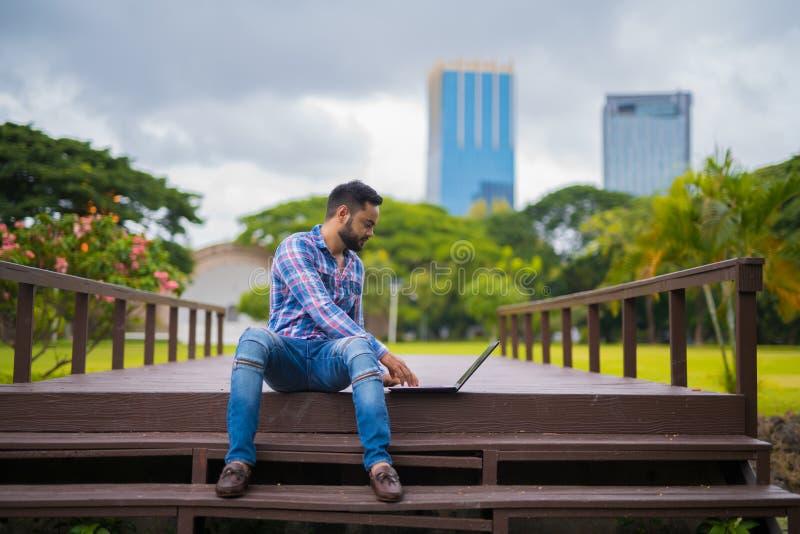 Giovane uomo indiano bello in parco facendo uso del computer portatile fotografie stock