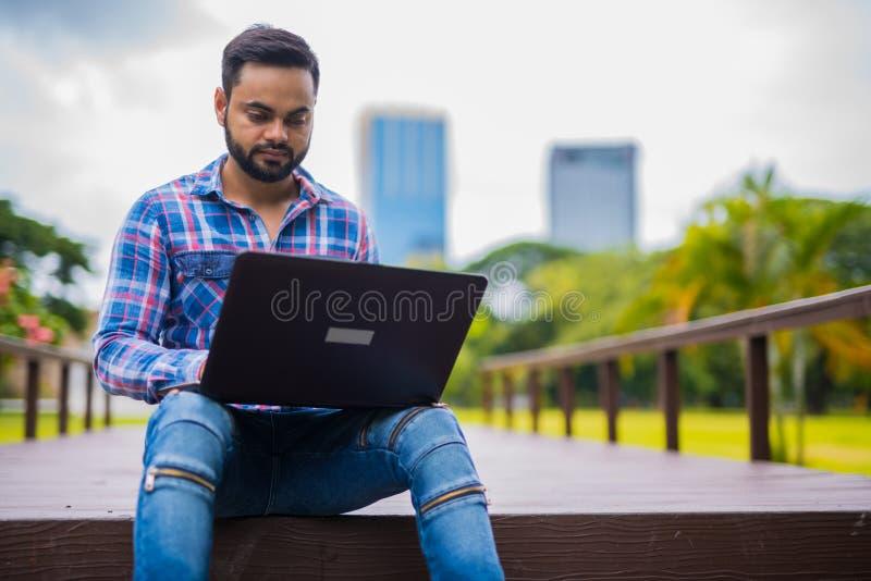 Giovane uomo indiano bello in parco facendo uso del computer portatile fotografie stock libere da diritti