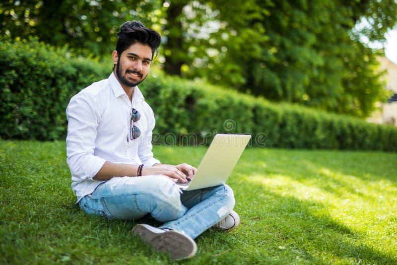Giovane uomo indiano computer portatile usando e di battitura a macchina nell'erba di estate nella via immagini stock libere da diritti