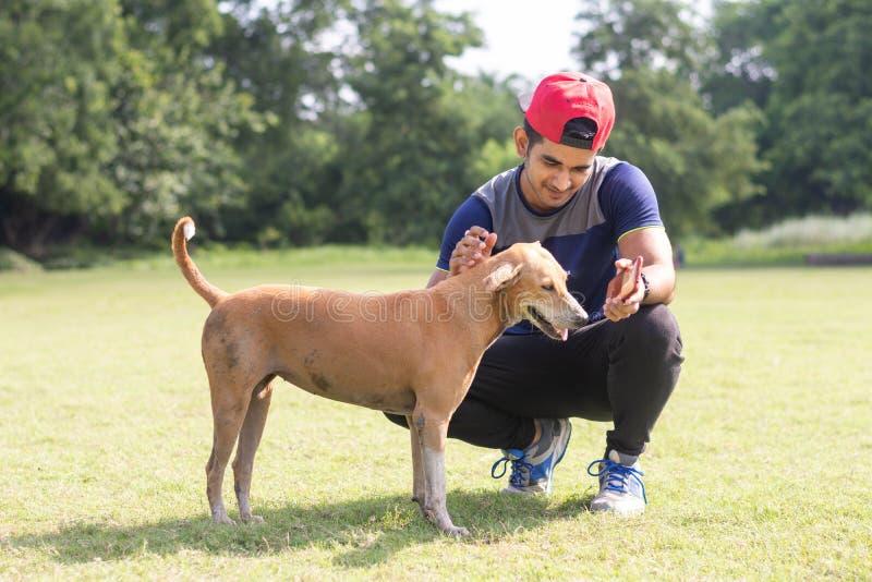 Giovane uomo indiano dell'atleta che gioca con il cane in campo sportivo mentre pareggiando Sport e concetto maschii di forma fis fotografia stock