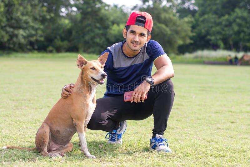 Giovane uomo indiano dell'atleta che gioca con il cane in campo sportivo mentre pareggiando Sport e concetto maschii di forma fis immagine stock libera da diritti
