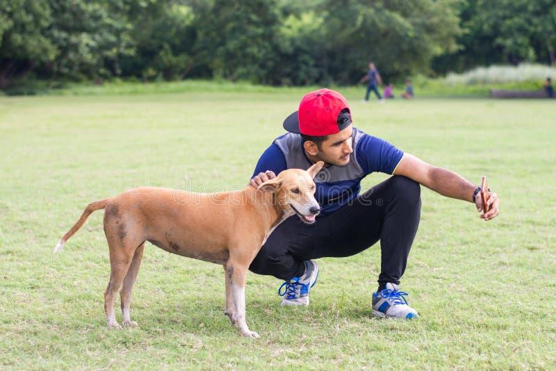 Giovane uomo indiano dell'atleta che gioca con il cane e che prende i selfies in campo sportivo mentre pareggiando Sport e concet fotografia stock