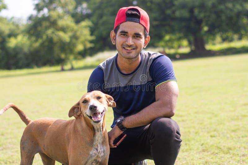 Giovane uomo indiano di sport che gioca con il cane in campo sportivo mentre pareggiando Sport e concetto maschii di forma fisica immagine stock