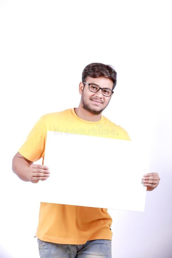 Giovane uomo indiano emozionante sugli occhiali e sulla mostra del manifesto in bianco a disposizione fotografia stock libera da diritti