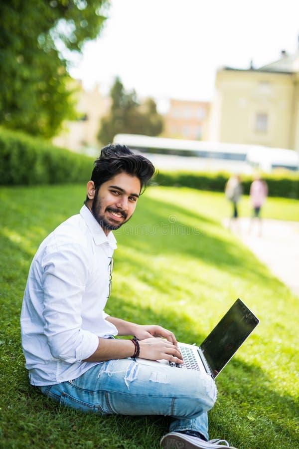Giovane uomo indiano facendo uso del suo computer portatile sull'erba su fondo urbano immagine stock libera da diritti