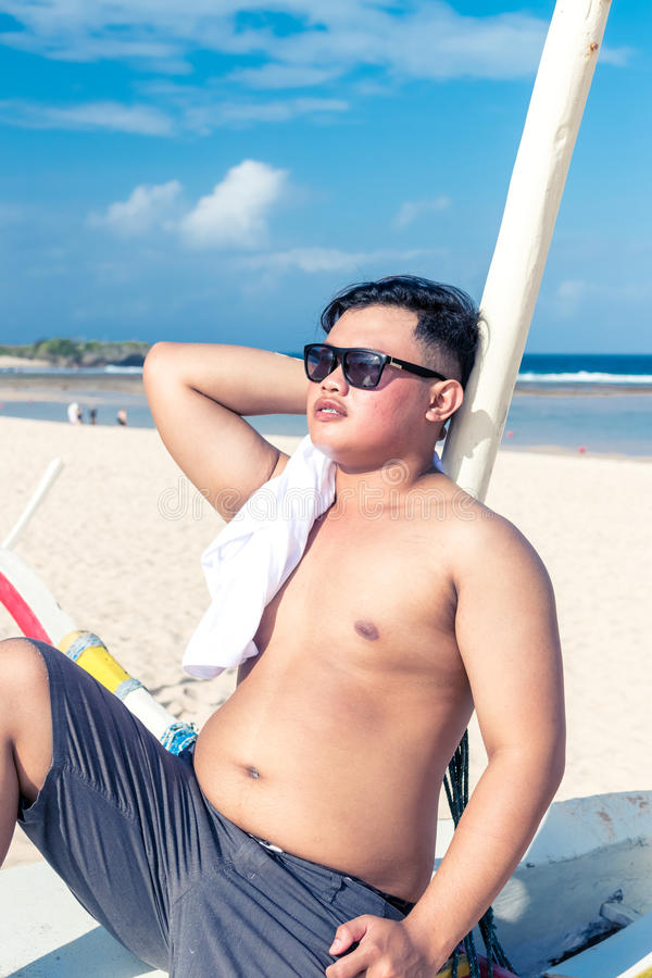 Giovane uomo indonesiano asiatico che si rilassa sulla spiaggia dell'isola tropicale di Bali, Indonesia fotografia stock libera da diritti
