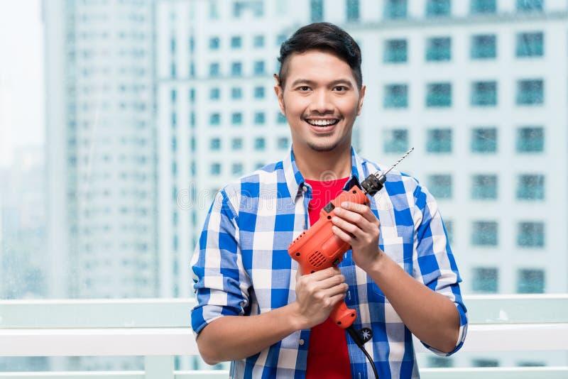 Giovane uomo indonesiano con il trapano fotografia stock