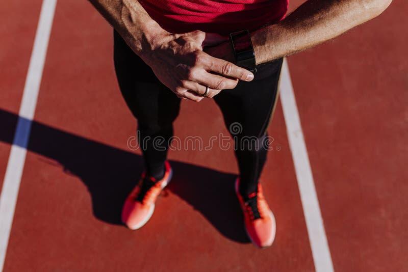 Giovane uomo irriconoscibile del corridore che controlla orologio astuto nel vicolo di atletica Sport all'aperto immagini stock libere da diritti