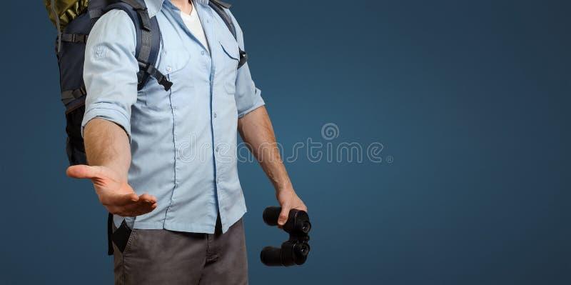 Giovane uomo irriconoscibile del viaggiatore con uno zaino ed il binocolo su fondo blu Allunga fuori la sua mano Aiuto nel viaggi immagine stock