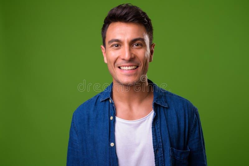 Giovane uomo ispano bello contro fondo verde immagini stock