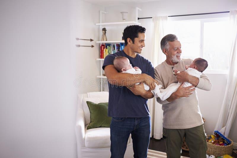 Giovane uomo ispano e suo il padre senior che tengono i suoi due neonati a casa immagini stock libere da diritti