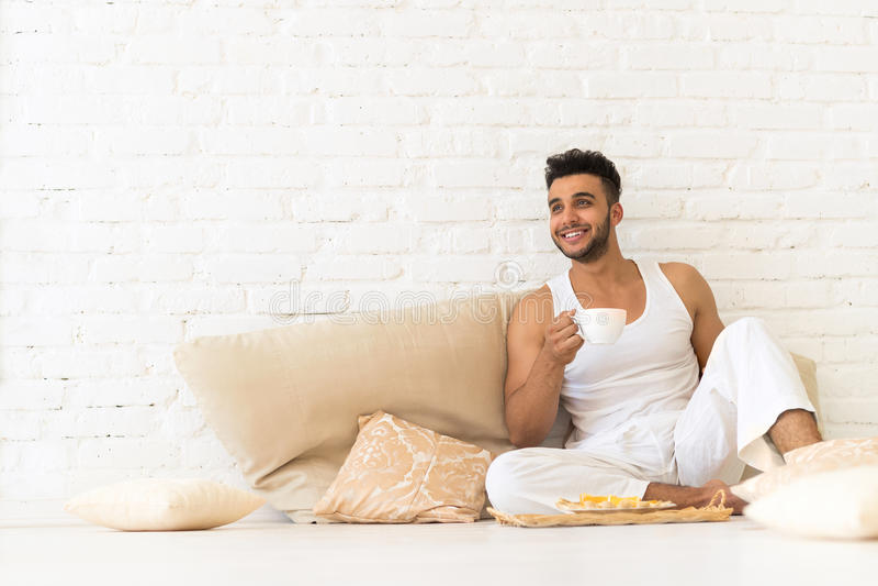 Giovane uomo ispano Sit On Pillows Floor, camera da letto sorridente felice dello spazio della copia di Guy With Breakfast Tray L immagine stock libera da diritti