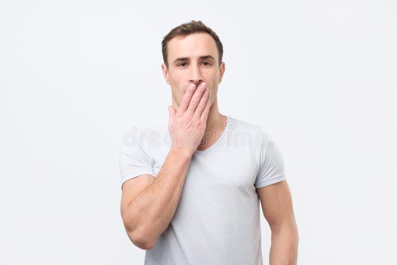 Giovane uomo italiano colpito nella bocca bianca della copertura della maglietta con le mani ed esaminare macchina fotografica immagini stock