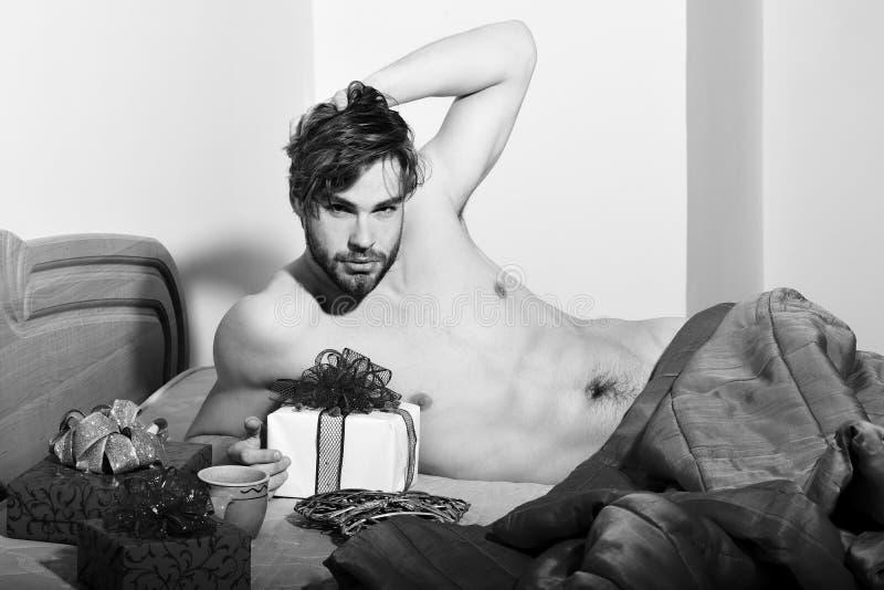 Giovane uomo macho sexy barbuto bello con la menzogne alla moda della barba nuda sul letto sotto la coperta rossa con i presente  fotografia stock