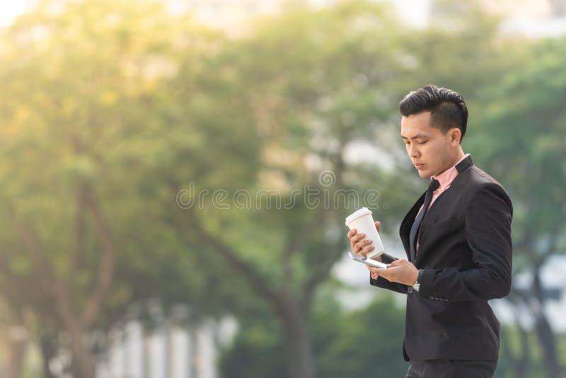 Giovane uomo malese di affari sul suo Smartphone con una tazza di caffè Copi lo spazio per testo fotografia stock libera da diritti