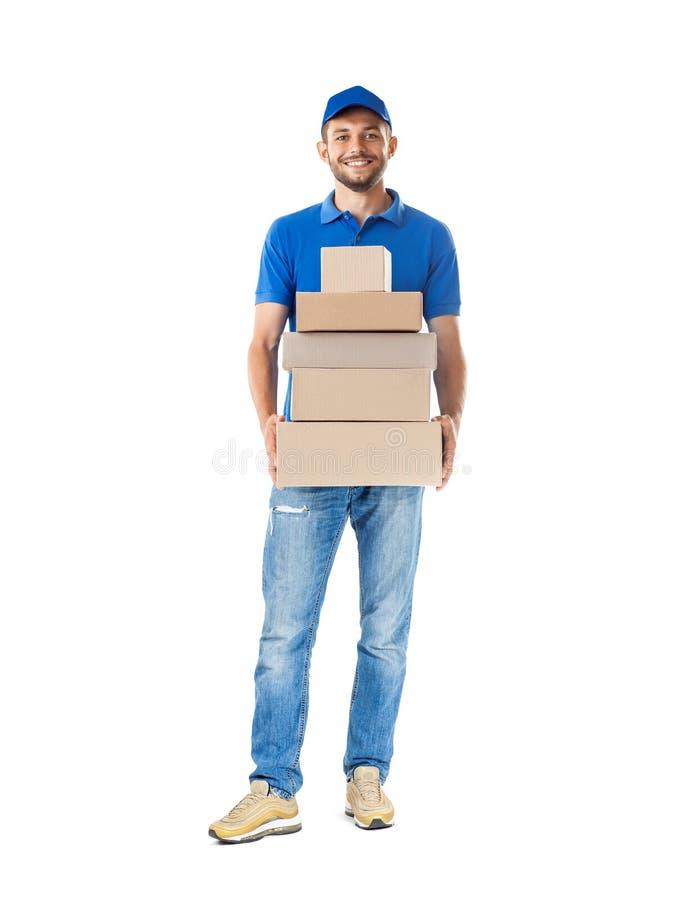 Giovane uomo maschio sorridente del corriere di distribuzione postale con la consegna della p fotografia stock libera da diritti