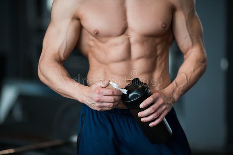 Giovane uomo muscolare che mostra il suo corpo perfetto Equipaggi bere da un agitatore di cocktail con la proteina fotografie stock